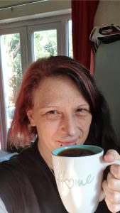 """Andi with cup of coffee in mug saying """"home"""""""