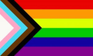 Inclusive Pride flag - white, pink, blue, brown and black lines in a triangle entering the Pride rainbow stripes