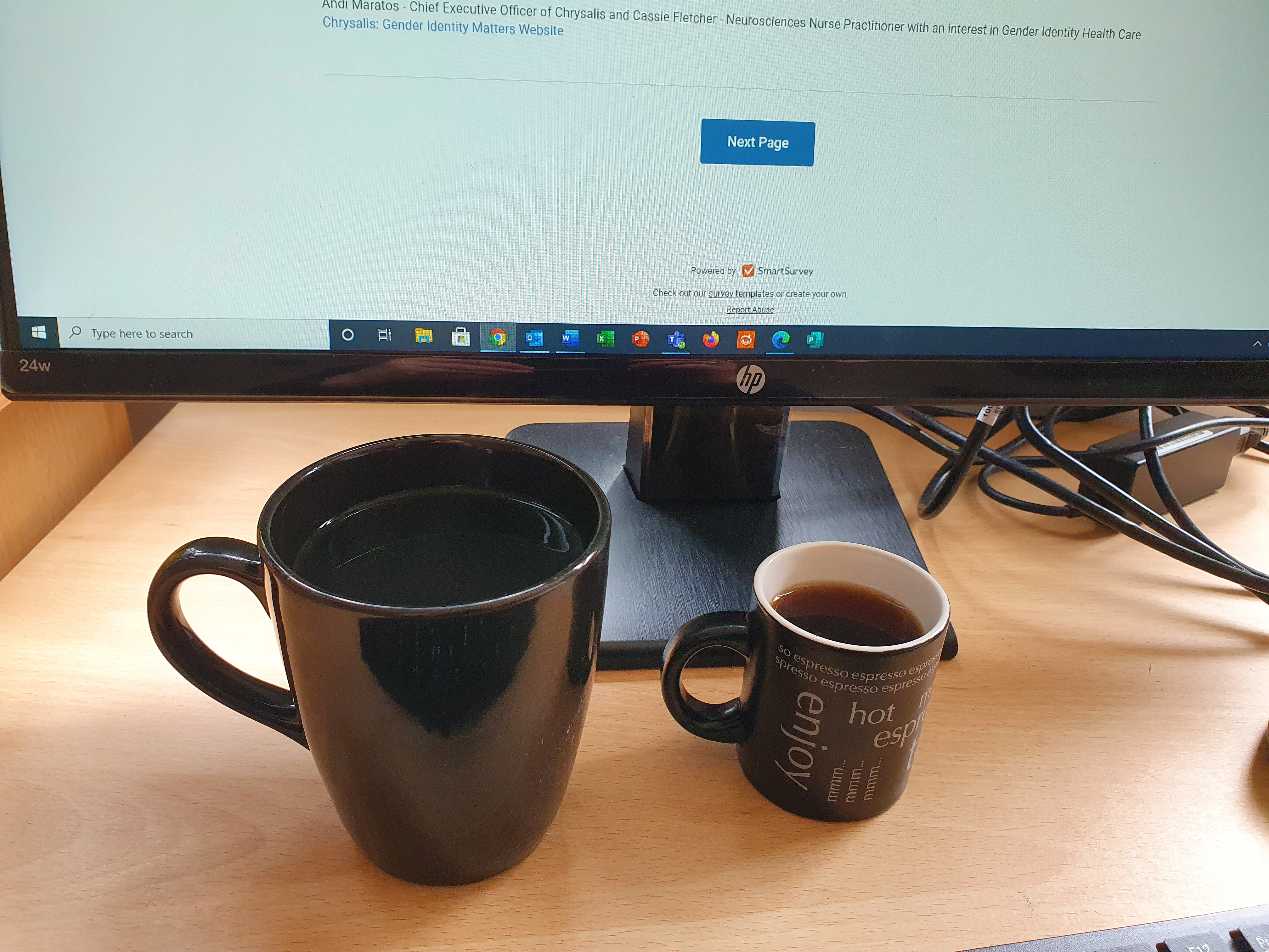 Large and small coffee cups in front of monitor