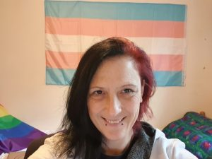 Andi with the trans flag in the background