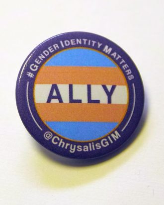 "Badge with trans flag surrounded by purple boarder, text on badge: ""Ally"", text encircling border ""#GenderIdentityMatters"" and ""@ChrysalisGIM"""