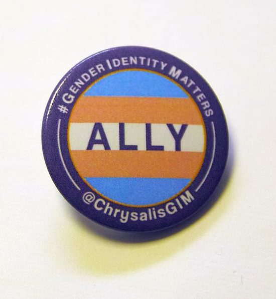 """Badge with trans flag surrounded by purple boarder, text on badge: """"Ally"""", text encircling border """"#GenderIdentityMatters"""" and """"@ChrysalisGIM"""""""