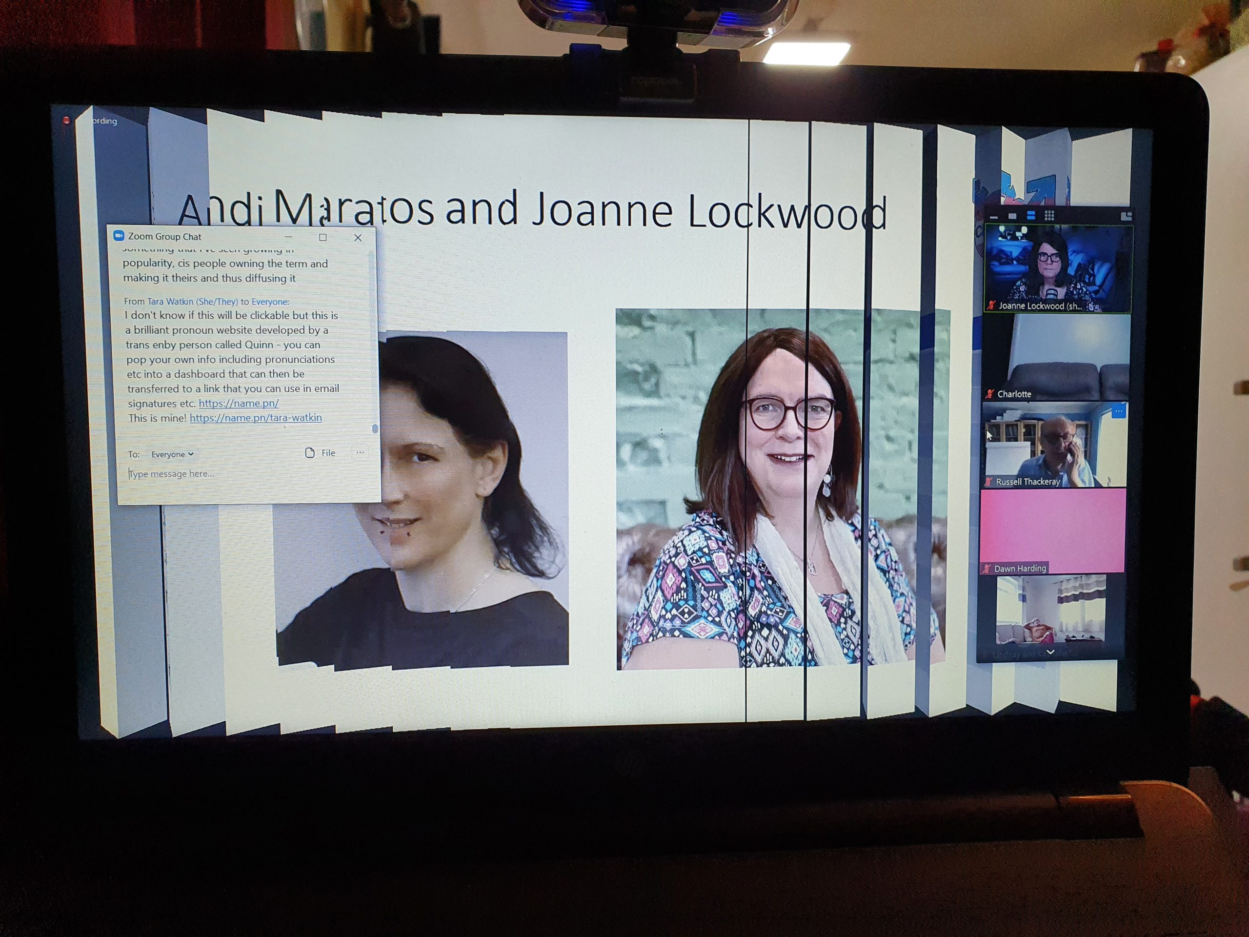 Zoom slide with Andi and Joanne's faces on it, slide just rotating to next image, chat window open and participants down right hand side