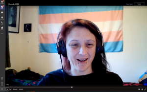 Screenshot of Andi with headphones on and trans flag in background presenting at the AGM. There is a cat asleep behind them