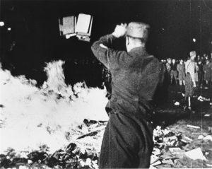 Nazi throwing more books onto a bonfire of books, people stood in background