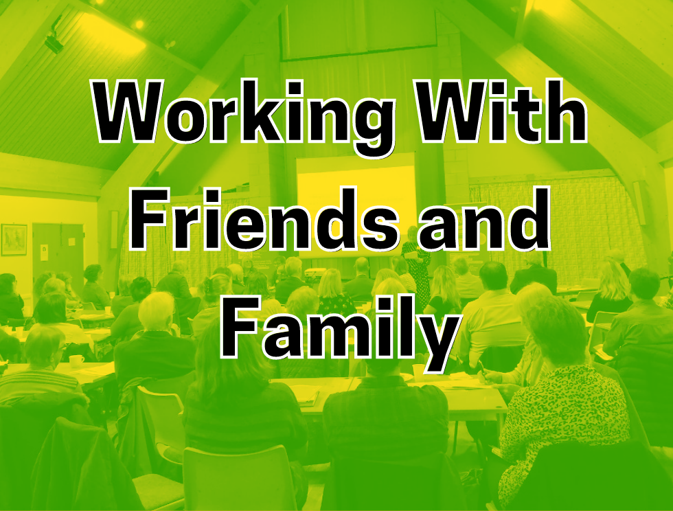 Working with friends and family: Room full of people watching presentation.